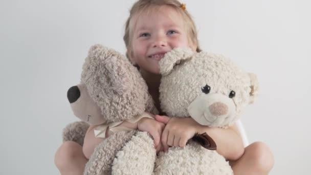 Egy boldog kislány öleli a plüssmacikat.