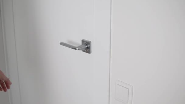 Ženská ruka otvírá světelné dveře u kliky.