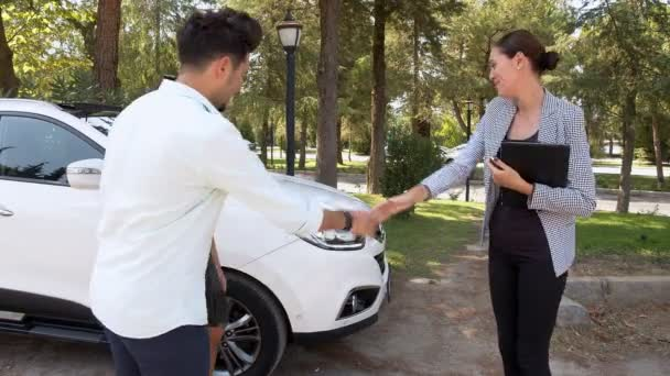 A Couple Purchases A New Car.Female car dealer meeting a young couple for presenting a white car.