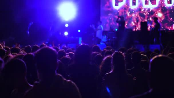 Élő koncert egy kiváló állomány videót, hogy a funkciók felvételt rajongók izgatottan emelése fel a kezét a levegőben egy koncerten. A lüktető spotlámpák azt mutatják, a sziluettje a közönség tapsolt izgatottan a koncert zene.