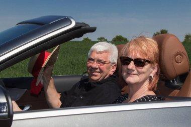 Happy senior couple in sports car