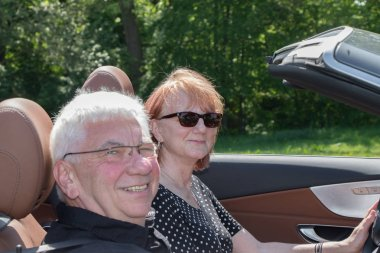 Happy older couple drives with a luxury convertible car on a sunny day