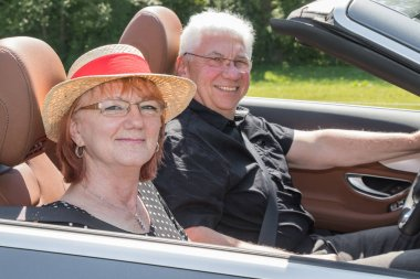 Two happy elderly people with a luxury convertible car