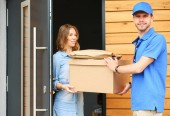 Photo Smiling delivery man in blue uniform delivering parcel box to recipient - courier service concept. Smiling delivery man in blue uniform