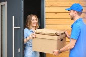 Fotografie Smiling delivery man in blue uniform delivering parcel box to recipient - courier service concept. Smiling delivery man in blue uniform