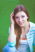 Fiatal nő ül a zöld füvön. Portreit fiatal nő