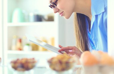 Portrait of female standing near open fridge full of healthy food, vegetables and fruits.