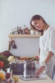 Főzés a konyhában fakanállal nő. Nő főzés
