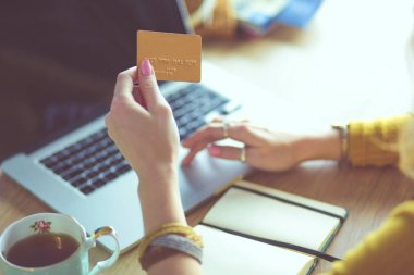 Young woman holding credit card and using laptop computer. Online shopping concept
