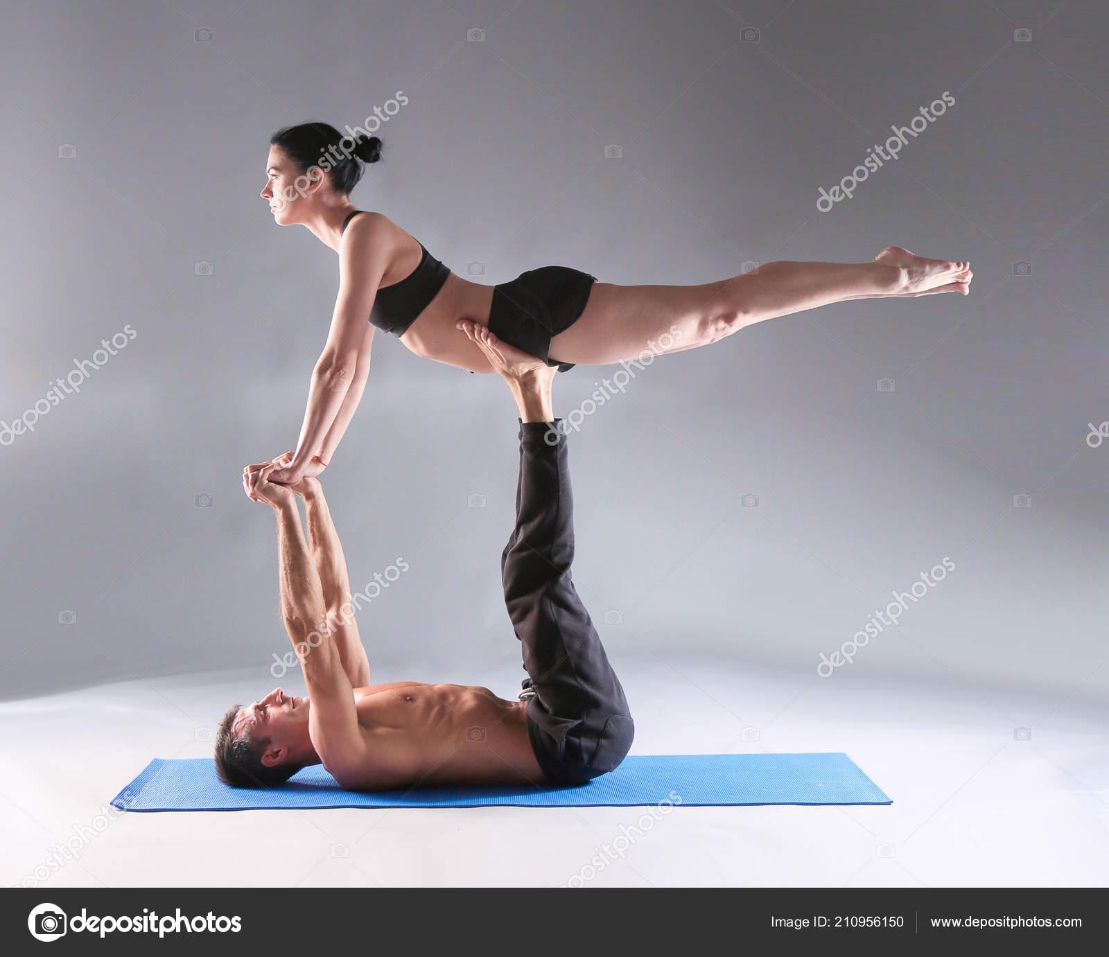 Pareja joven practicando yoga acro en mat en estudio juntos. Acroyoga. Yoga  en pareja f432f19fe1bb