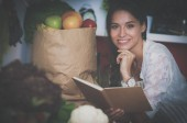 Fotografie mladá žena čte kuchařka v kuchyni, hledá receptレシピをお探しで若い女性が台所で料理の本を読んで
