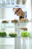Fotografie Portrét ženy stojící poblíž otevřené lednice plná zdravých potravin, zeleniny a ovoce