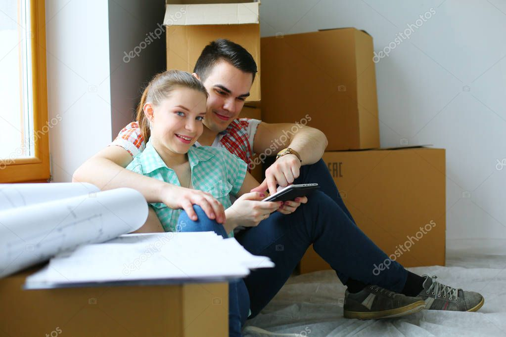 Couple moving in house sitting on the floor with ipad. Couple.