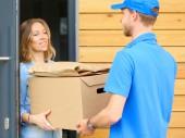 S úsměvem doručovatel v modré uniformě přináší balík box příjemci - kurýrní služby koncept. S úsměvem doručovatel v modré uniformě
