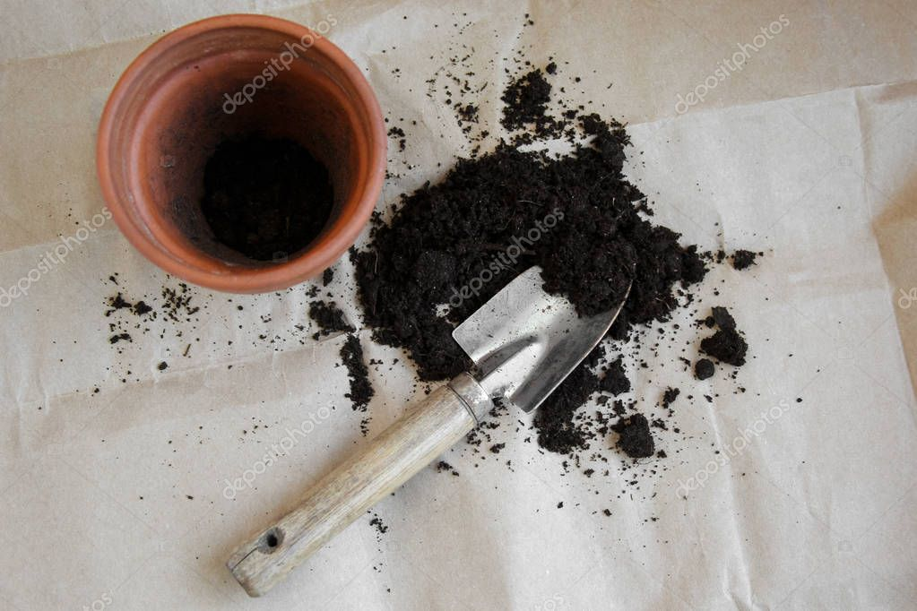 Flower pot with soil and a shovel on a light background. Gardening.