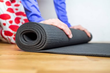 Time for meditation. Girl rolling fitness mat before, after class at home on wooden floor. Hands and legs close up, focus on mat