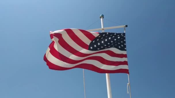 American flag waving in the wind in front of blue sky