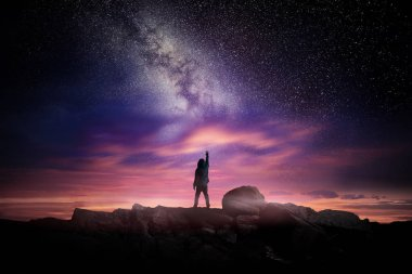 Night time long exposure landscape photography. A man standing in a high place reaching up in wonder to the Milky Way galaxy, photo composite.