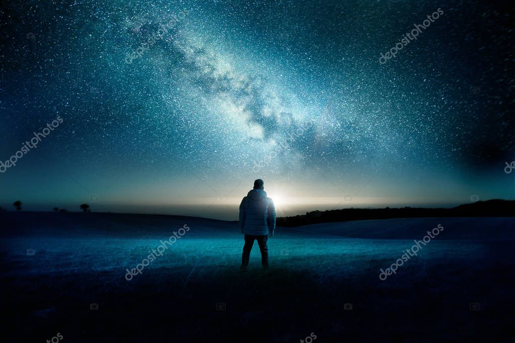 A man stands watching with wonder and amazement as the moon and milky way galaxy fill the night sky. Night time landscape. Photo composite.