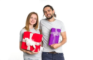 Loving couple. Man and woman with a gift in their hands on light background. Christmas, New Year, Valentine day, holiday gift, shopping.