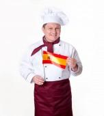 Koch kocht mit der Flagge Spaniens auf hellem Hintergrund. Mann mittleren Alters.