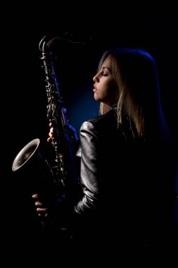 Saxophonist, illuminated by blue and white light