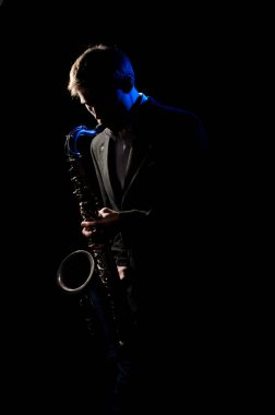 Saxophonist, illuminated by blue and white light, plays a melody on a black background