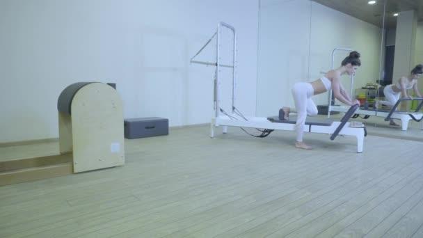 Cvičení Pilates. Žena v bílých šatech cvičí protahovací cvičení na reformátora v tělocvičně. všechny série podle čísla 01234567890001.