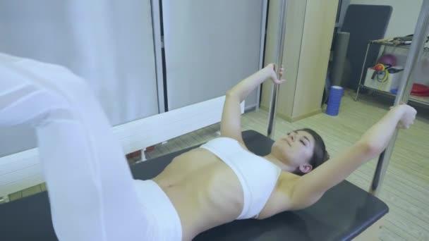 Pilates. Nő a fehér ruhákat gyakorló nyújtó gyakorlása a tornateremben reformátor. minden sorozat szám 01234567890001.