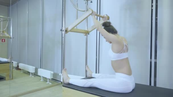 Pilates. Woman in white clothes practicing stretching exercise on reformer in gym. all series by number 01234567890001.
