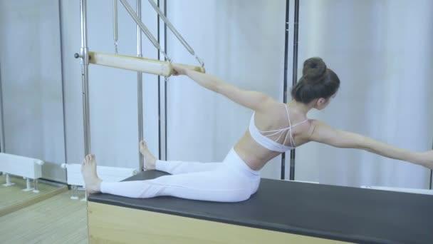 Cvičení Pilates. Žena v bílých šatech cvičí protahovací cvičení na reformátora v tělocvičně. všechny série podle čísla 01234567890001