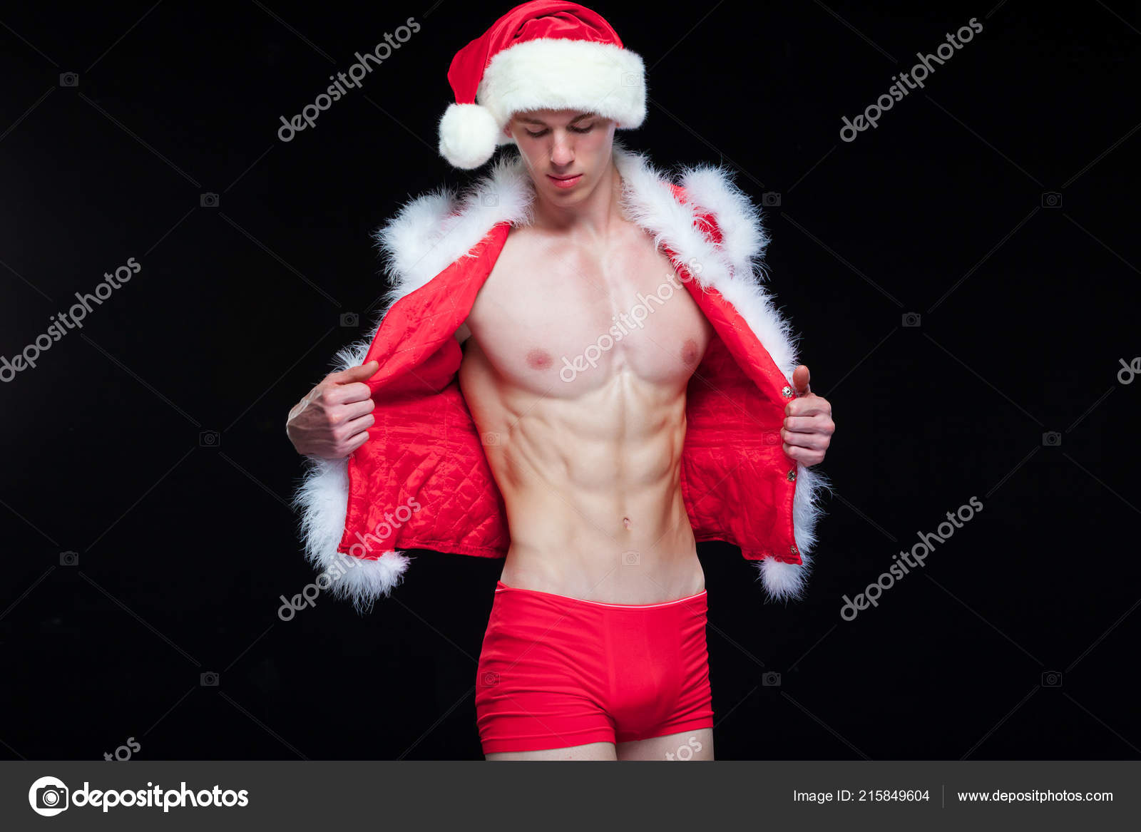 09e94812a7d43 Sexy Santa Claus . Young muscular man wearing Santa Claus hat demonstrate  his muscles. Isolated