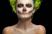 Fotografie Halloween. Portrait of young beautiful girl with make-up skeleton on her face. And green hair. Isolated on black background.