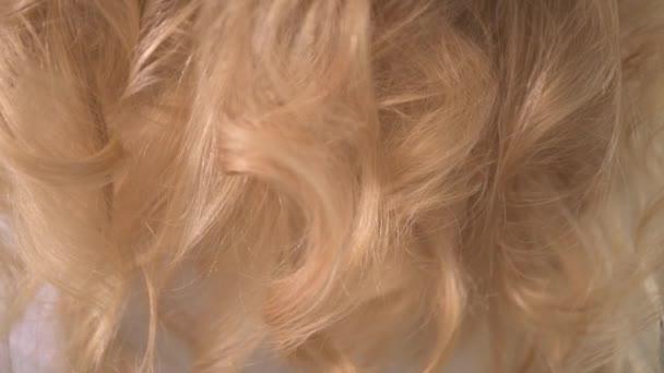 Krásné dlouhé blond vlasy. Vlasy kadeře. Bílé kadeře.
