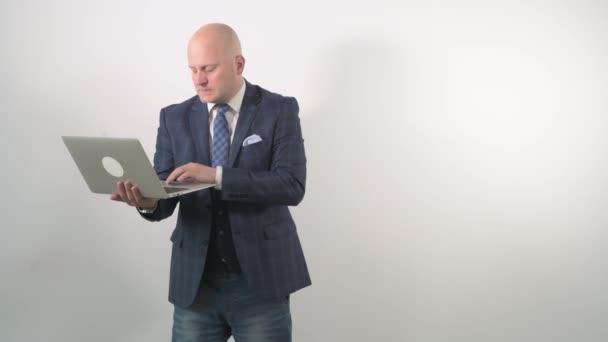Šokovaný obchodník s laptopem v ruce se ptá na špatně odvedenou práci.