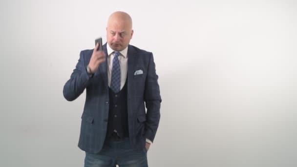 Smějící se dospělý muž v bundě a džínách mluví na mobilním telefonu.