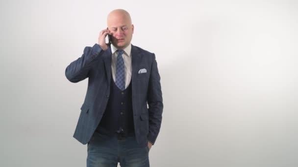Dospělý muž v bundě mluví po telefonu s úžasem ve tváři.