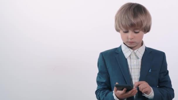 Meglepett szőke fiú nyitott szájjal mobilt tart a kezében..