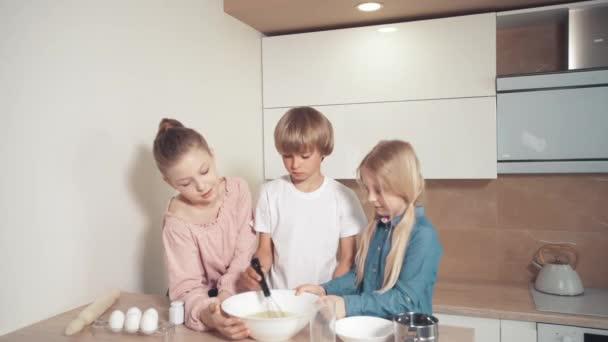Roztomilé děti připravují těsto na pizzu, koláč a sušenky v kuchyni.