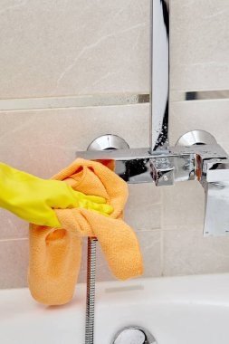 Professional housekeeping. Wipe the faucet in the bathroom with a dry towel.