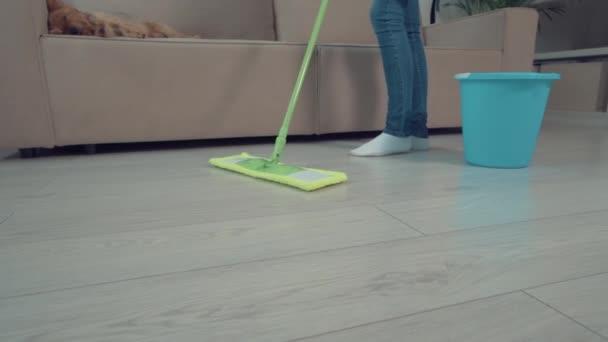 Mädchen wäscht den Boden im Wohnzimmer mit einem Wischmopp neben einem Eimer Wasser.