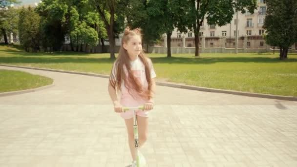 Egy gyönyörű barna lány körülnéz, robogózik és élvezi a jó időt..
