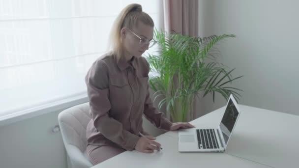 Eine schöne junge Frau sitzt an einem Schreibtisch und kommuniziert per Video. Blonde Frau.