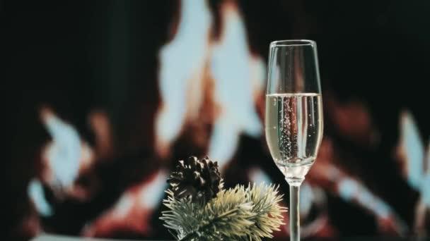 Bublinky šampaňského ve sklenici. Krb hoří v pozadí.