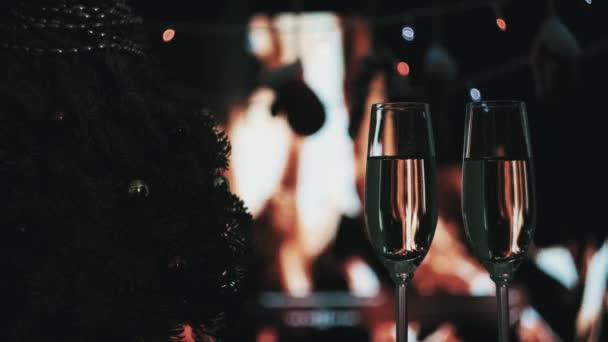 Dvě vysoké sklenice šampaňského. Ve tmě v noci, vánoční stromek.