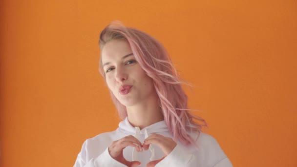 Mladá žena vyznává svou lásku. Ruce složené ve tvaru srdce.