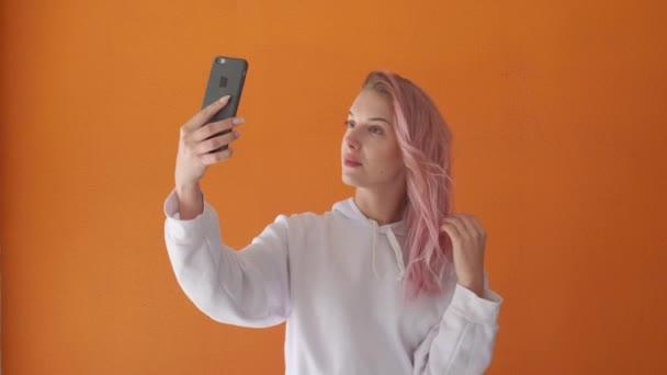 Schöne junge Frau macht ein Selfie. Haare entwickeln sich im Wind.