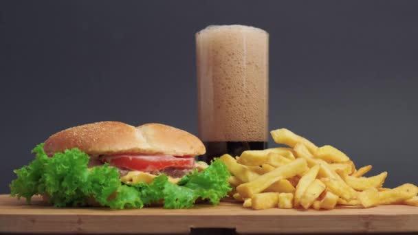 Na dřevěném stole je sendvič a hranolky. Vedle ní je sklenice limonády.