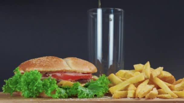 Auf dem Tisch liegen ein Sandwich und Pommes, ein Glas Limo. Spritzer fliegen zur Seite