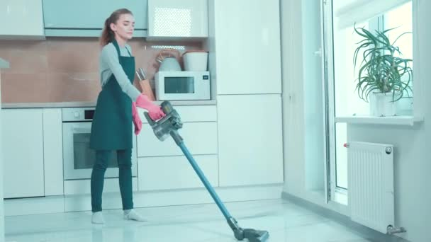 Krásná mladá žena vysává v kuchyni. Domácí práce.